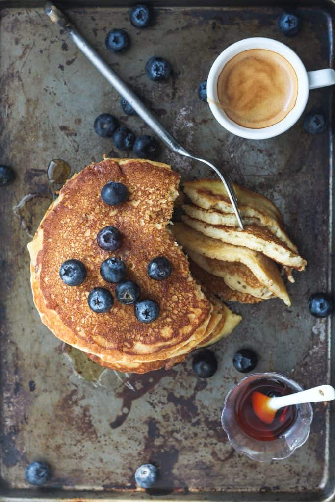 Pancakes made with sparkling water and buttermilk, on a distressed bakign sheet with espresso and maple syrup and blueberries