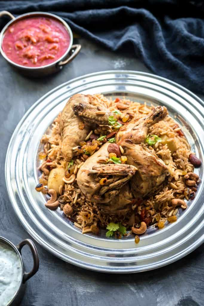 Chicken on a bed of spiced kabsa rice with mixed nuts and raisins, with two small bowls of tomato sauce and yogurt on the side.