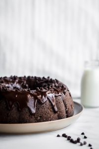 Chocolate Bundt Cake on a plate with chocolate chips and a bottle of milk in the background