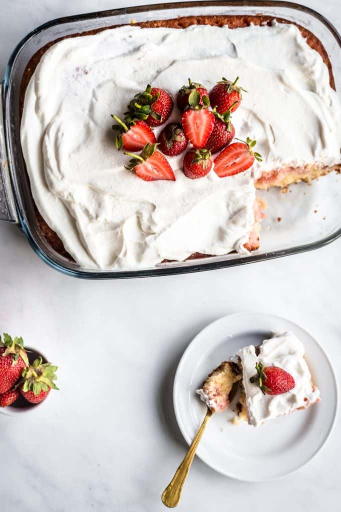 Strawberry cake photographed from the top with a small white plate holding a slice of cake, and a small bowl of strawberries