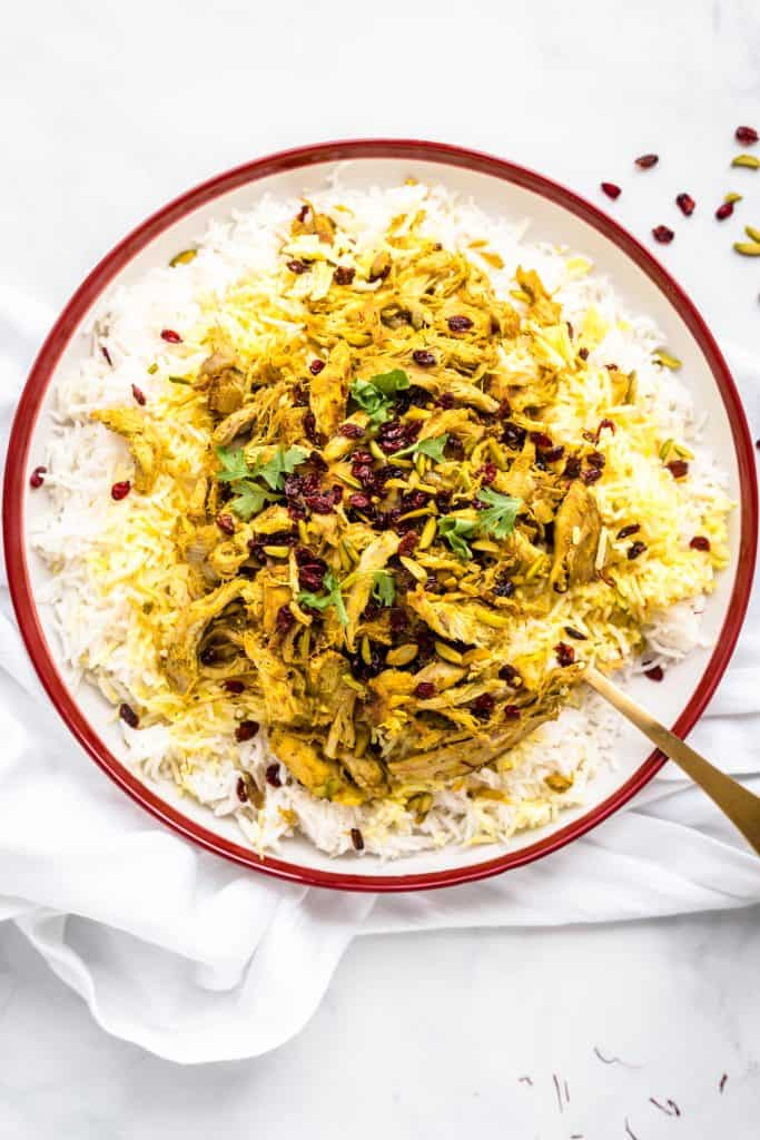 Plate of white rice topped with saffron rice, with the iranian style shredded chicken on top. On a white kitchen towel and a white background.