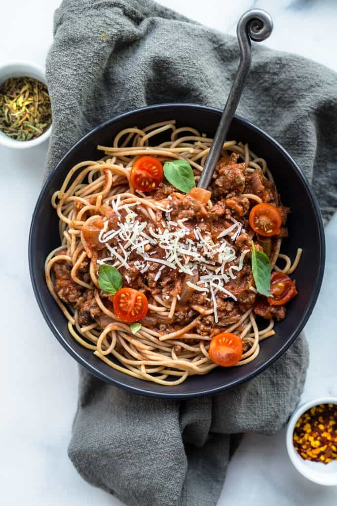 A plate of spaghetti bolognese on a gray kitchen towel with herbs at the side