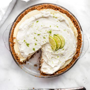 key lime pie with a slice cut out of it on a white background