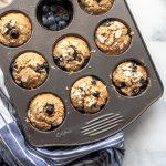 Muffin tray full of healthy blueberry muffins on a blue kitchen towel