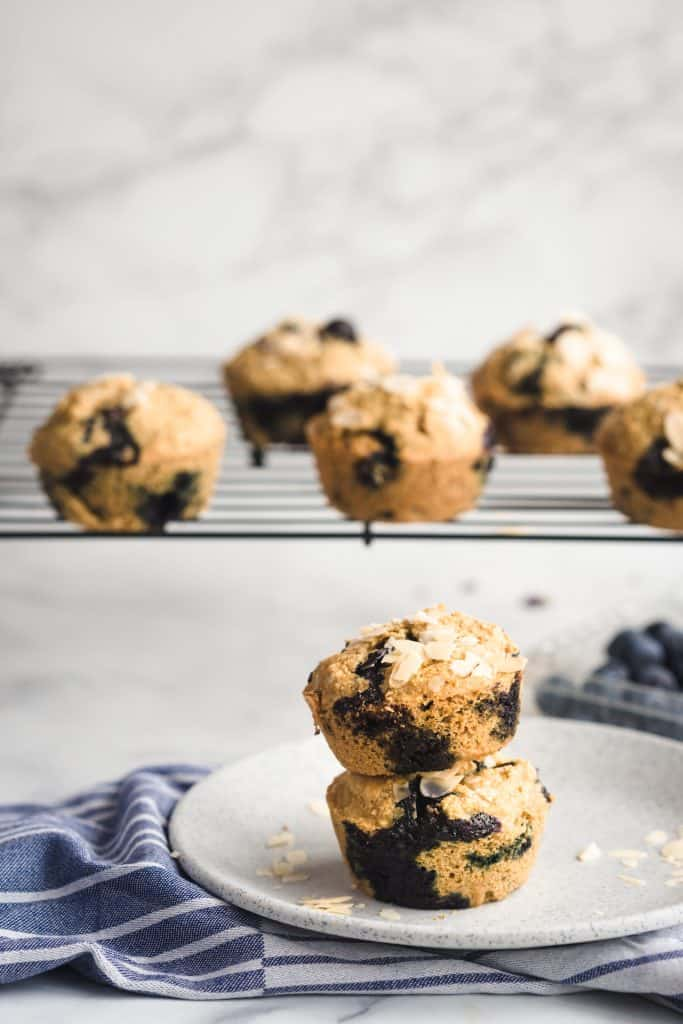 Healthy blueberry muffins stacked on a plate with more muffins on a cooling rack behind it