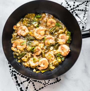 A skillet filled with honey garlic prawns over a patterned kitchen towel