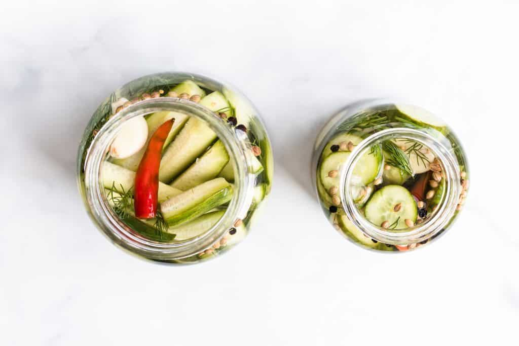 overhead shot of two jars filled with dill pickles on a white background