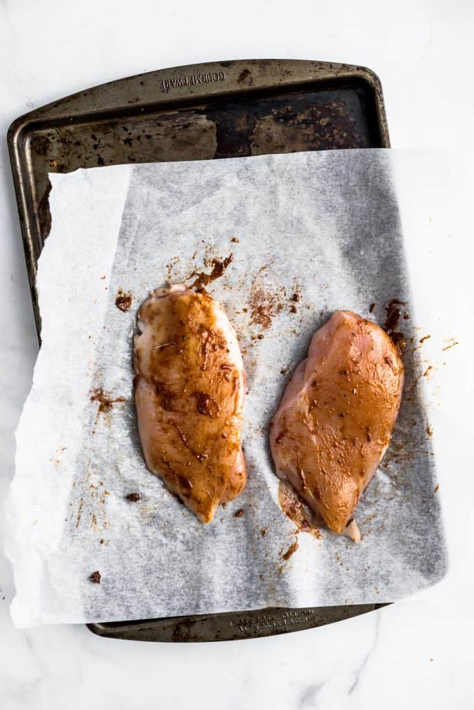 Raw chicken breasts with a spice rub on a baking sheet
