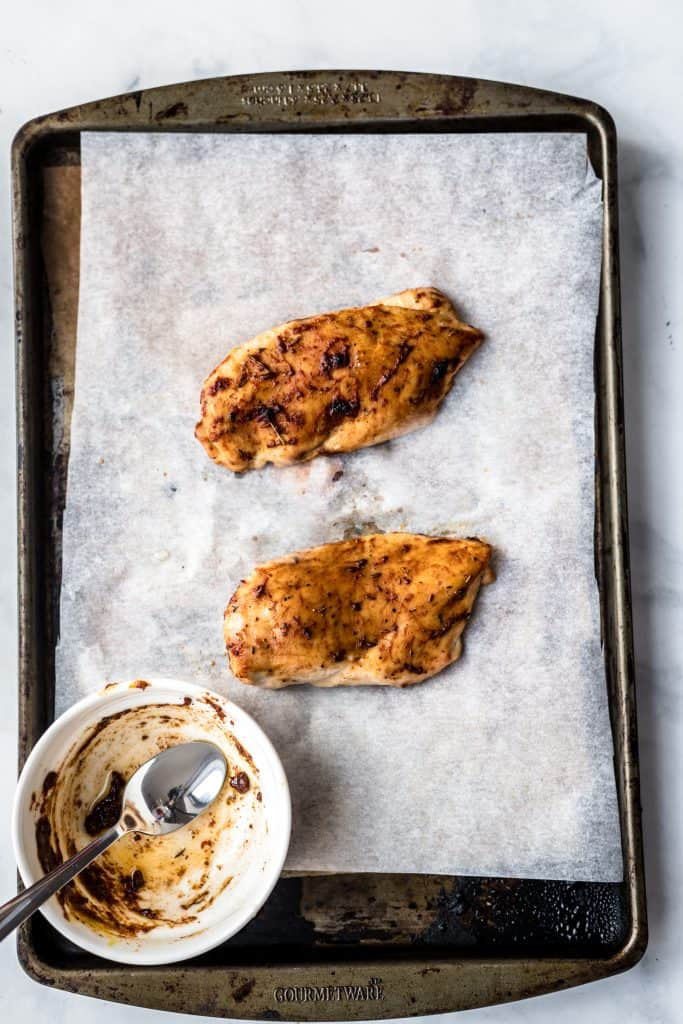 Baked chicken breasts for two on a parchment paper lined baking sheet