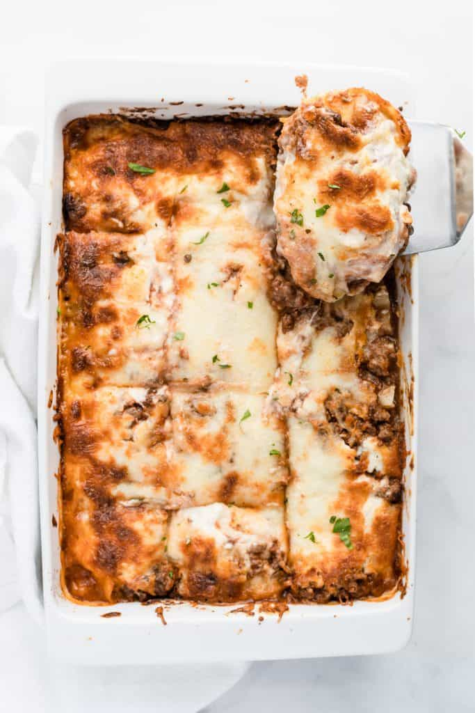Lasagna slice being lifted out of a whole lasagna on a white baking dish