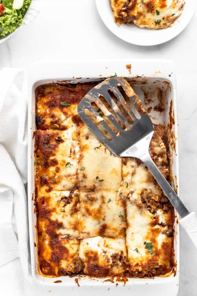 Lasagna bolognese in white baking pan with a piece taken out and a metal spatula on the pan