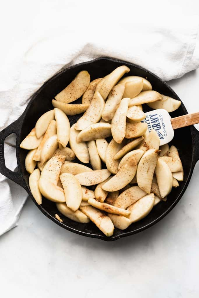 Raw apple slices sprinkled with cinnamon in a cast iron skillet