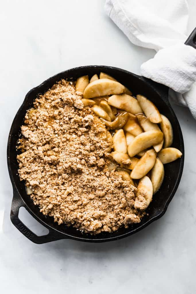 Half covered apple slices with apple crumble in cast iron skillet