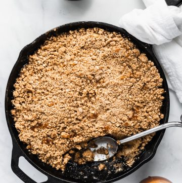 Salted Caramel Apple Crumble in a cast iron skillet with a scoop taken out and a plate with crumble and ice cream on teh side