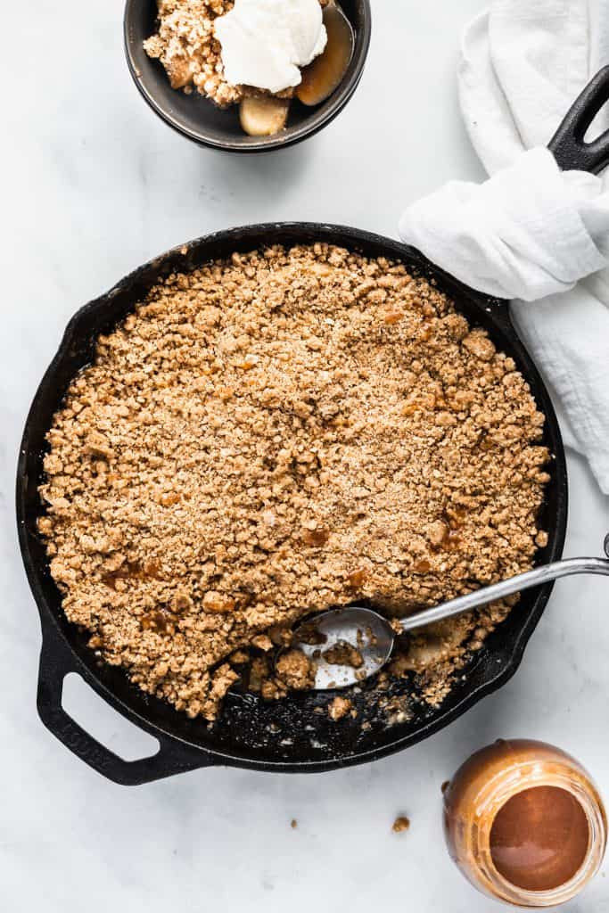 Apple crumble in a cast iron skillet with a scoop taken out