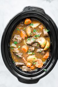 Slow cooker full of slow cooker beef stew with a ladle scooping some out