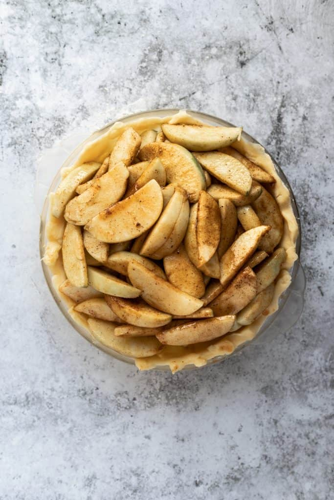 apples tossed with cinnamon in an unbaked pie crust