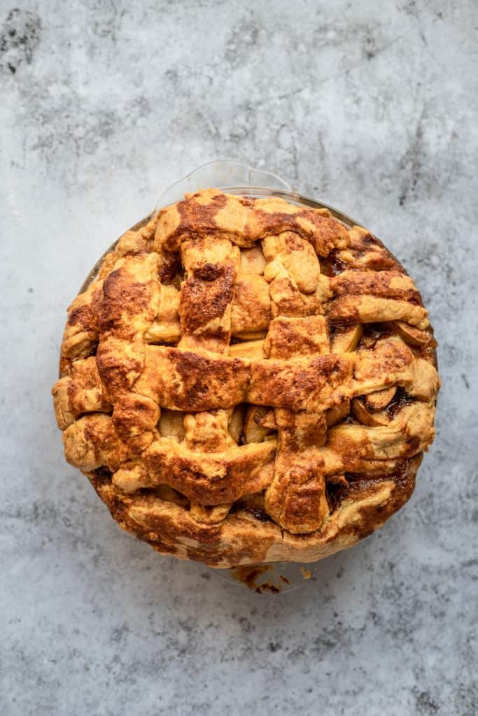 A whole easy apple pie on a pie plate with a plain gray background