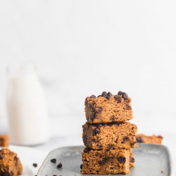healthy pumpkin bars stacked with a glass of milk at the back
