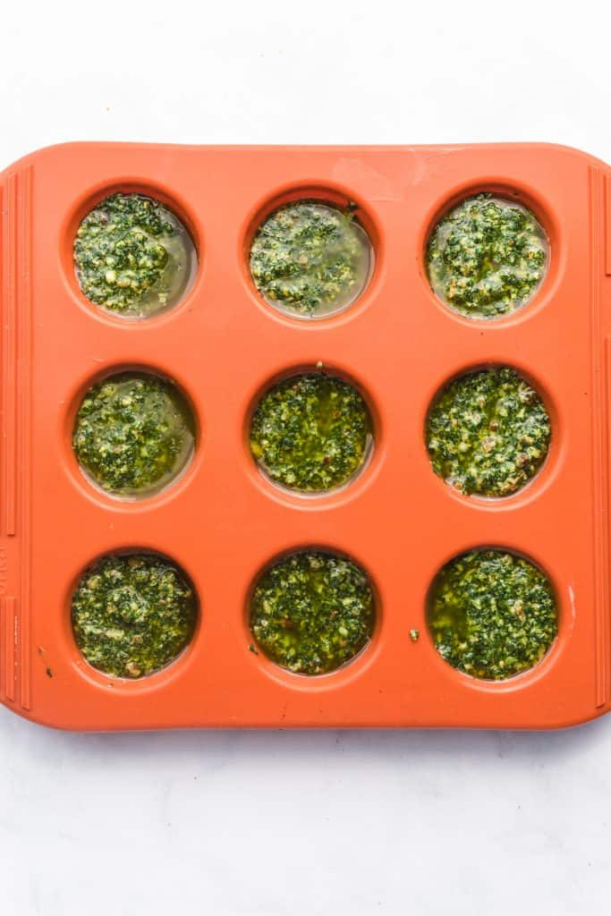 Pesto sauce portioned into a freezer safe container