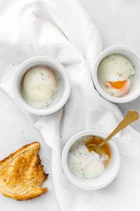 Three sous vide eggs in ramekins with a piece of bread