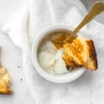 Sous vide egg in ramekin with runny yolk and a piece of bread