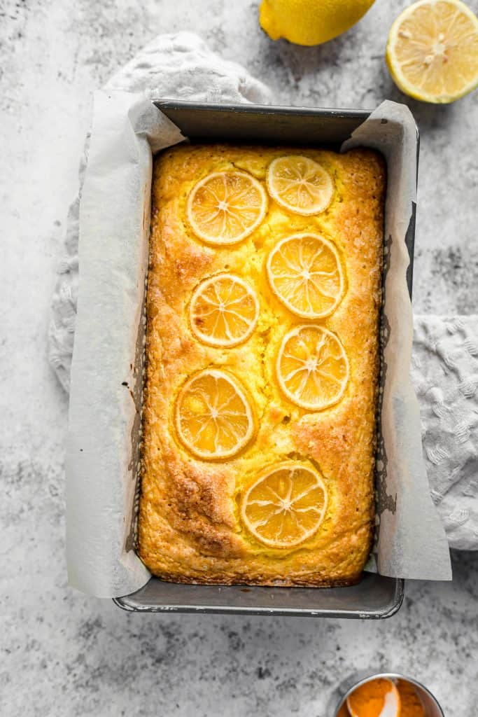 Baked lemon turmeric loaf cake in loaf pan with lemons in the background