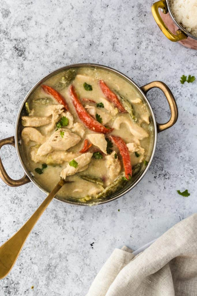 Thai Green Chicken Curry in a pan with cauliflower rice on the side