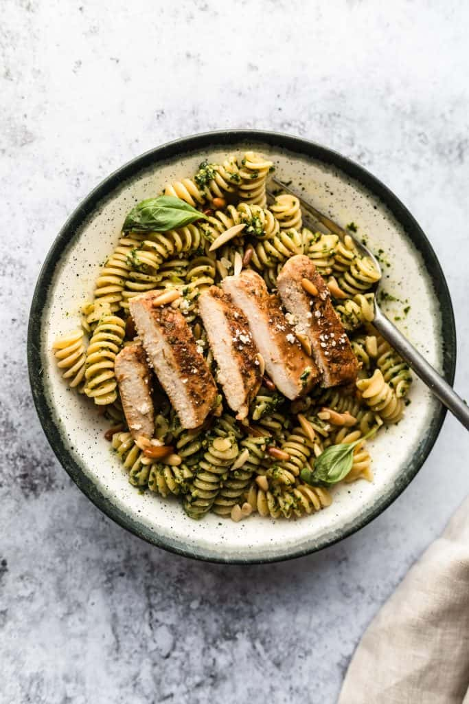Bowl of basil chicken pesto pasta with a fork in it, and a crumpled kitchen towel