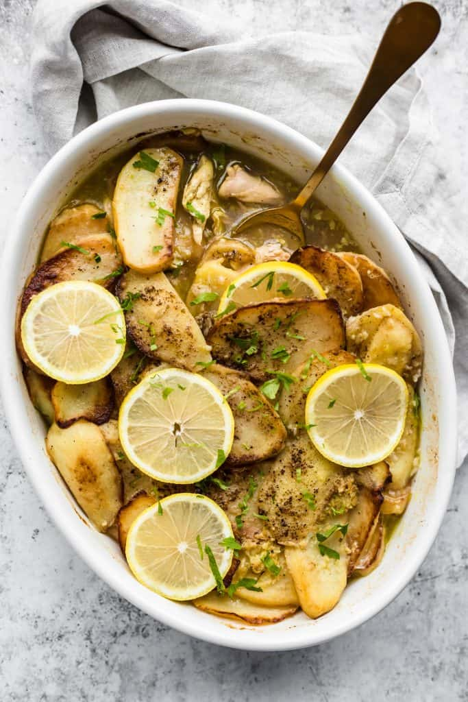 Baking dish with Lebanese chicken and potatoes with a spoon scooping some out