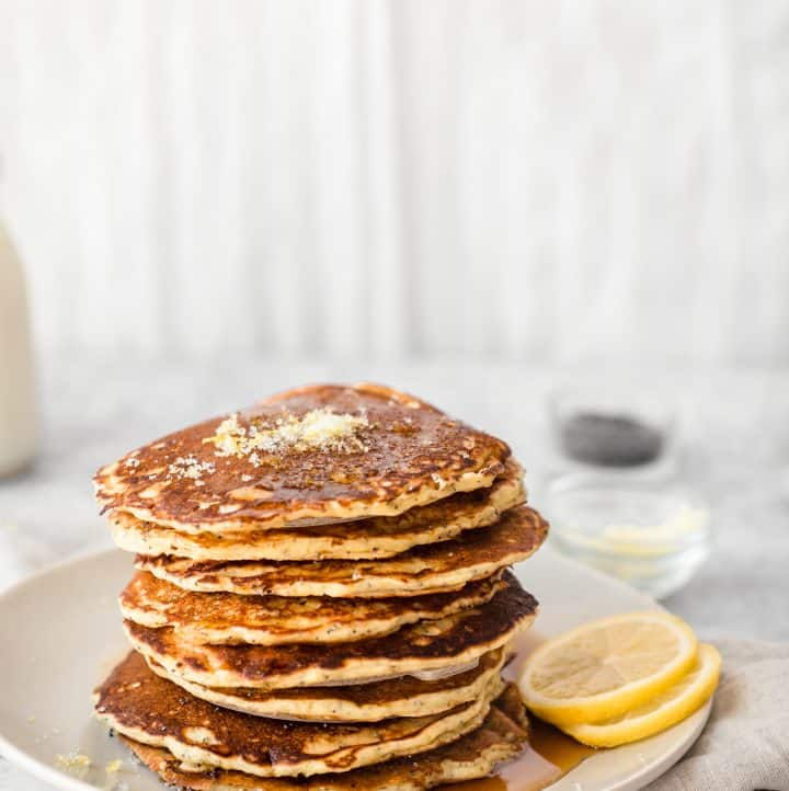 stack of lemon poppyseed pancakes on a plate with lemon slices and a kitchen towel