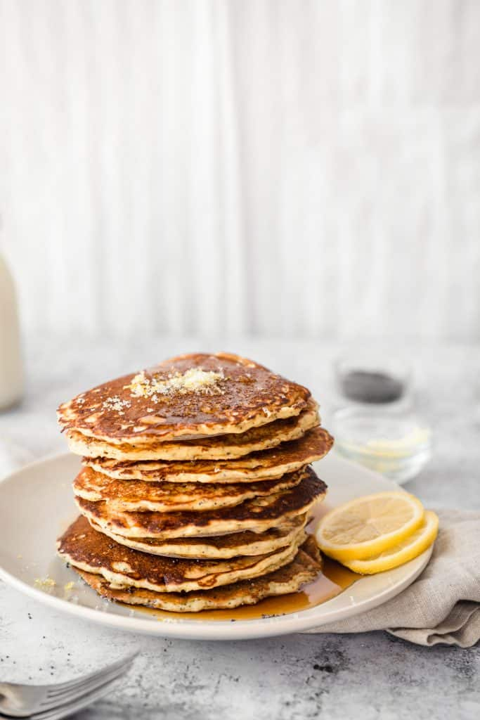 lemon poppyseed pancakes on a plate with maple syrup