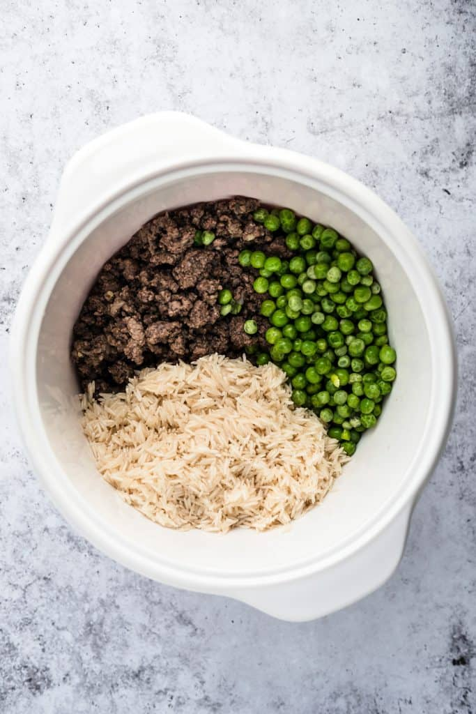 Lebanese rice, ground meat and peas in a pot before being cooked