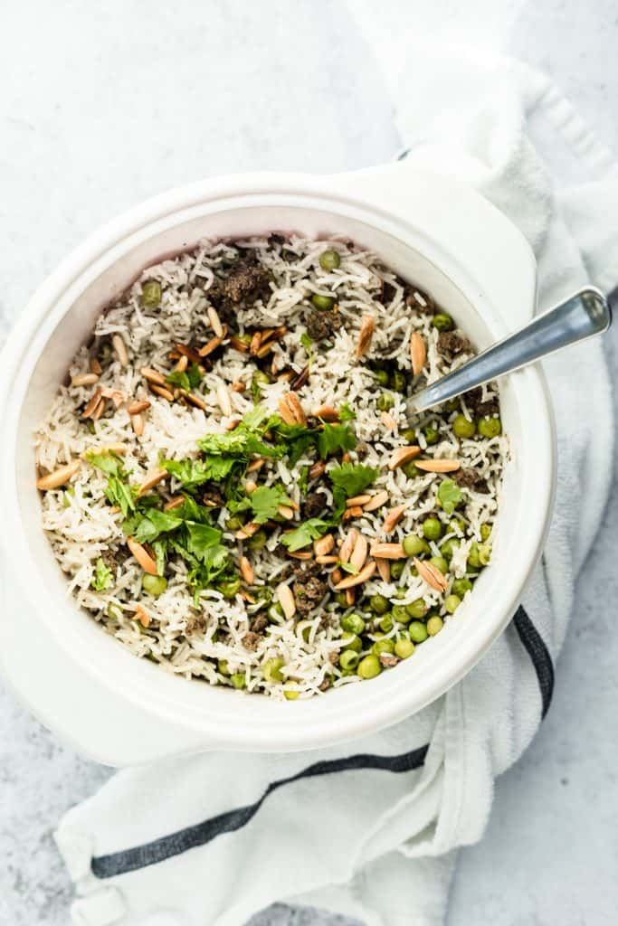 Pot of Lebanese rice hashweh with toasted nuts and parsley on top