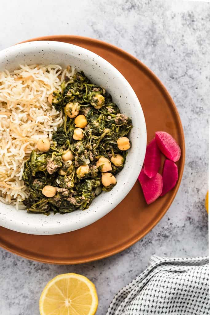 A bowl of Lebanese spinach stew with vermicelli rice on a plate with pickles and lemon slices