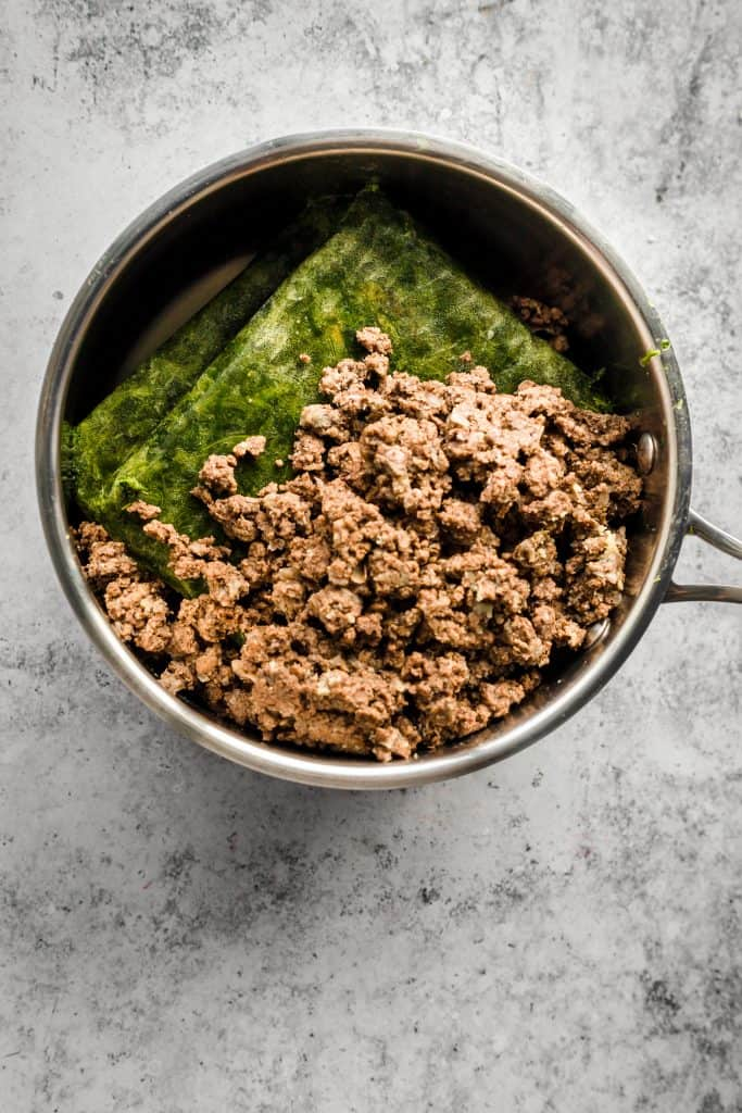 Spiced ground beef and frozen spinach in a saucepan for Lebanese spinach stew