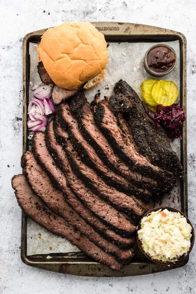 Sliced cooked sous vide brisket on a tray with bread buns, pickles and barbecue sauce