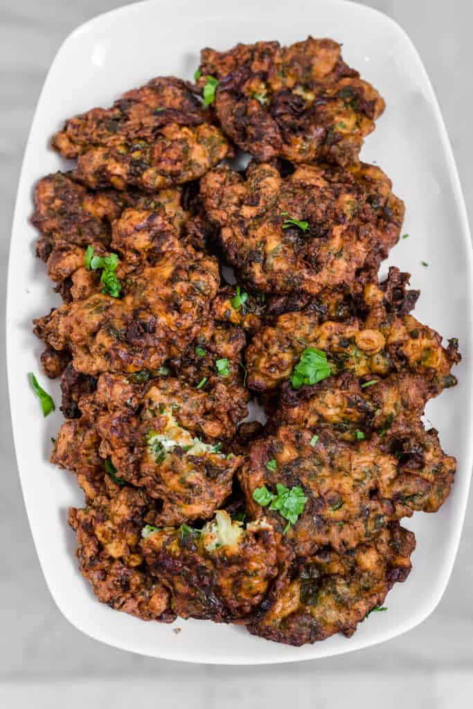 A platter full of fritters with parsley on top