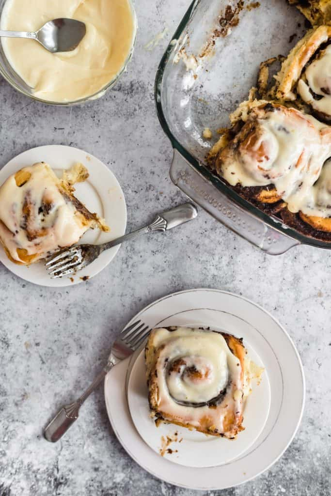 Baked cinnamon rolls in a pan and one on a plate with cream cheese frosting