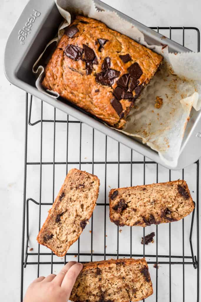 Little hand reaching for a slice of moist chocolate chip banana bread