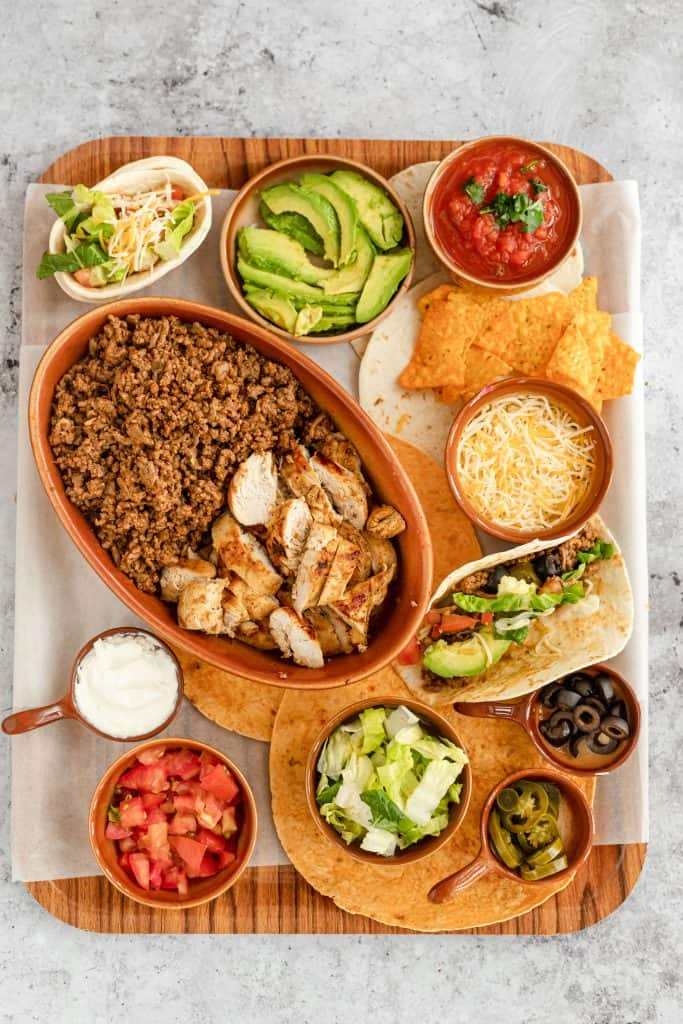 cooked chicken and beef taco mixture with toppings on a tray