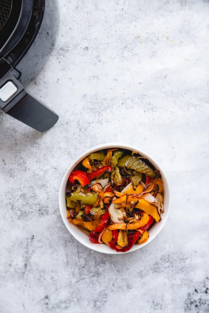 bowl of air fryer peppers with air fryer in background