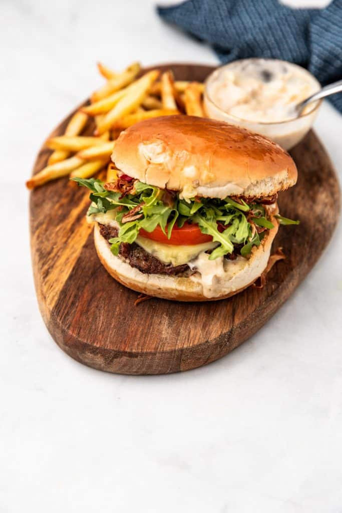 air fryer burger on wooden plate with fries