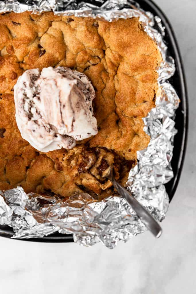 Zoomed in shot of pizookie in air fryer basket with scoop of ice cream