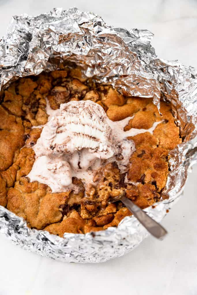 Zoomed in shot of pizookie in foil with scoop of ice cream