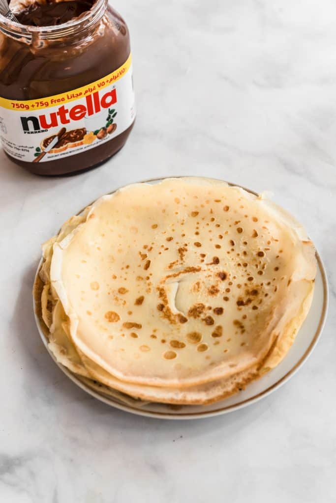 crepes stacked on plate with nutella jar in background