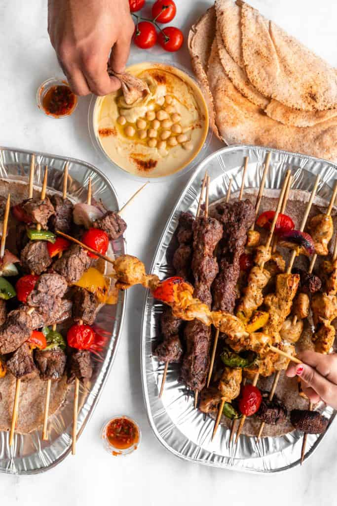 Aluminum platters with mixed arabic grills and a bowl of hummus and pita bread