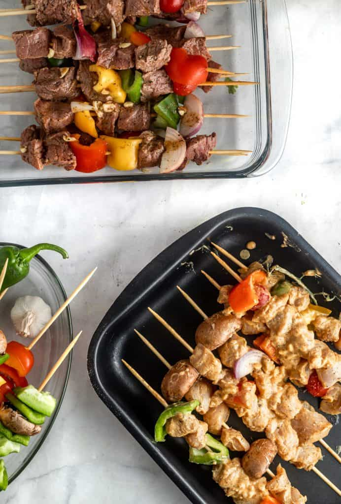 raw chicken and lamb assembled skewers in a pan