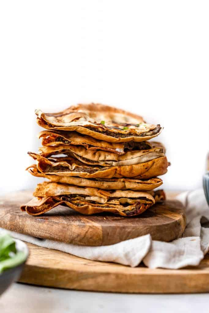 close up shot of arayes stacked on top of each other on wooden plate