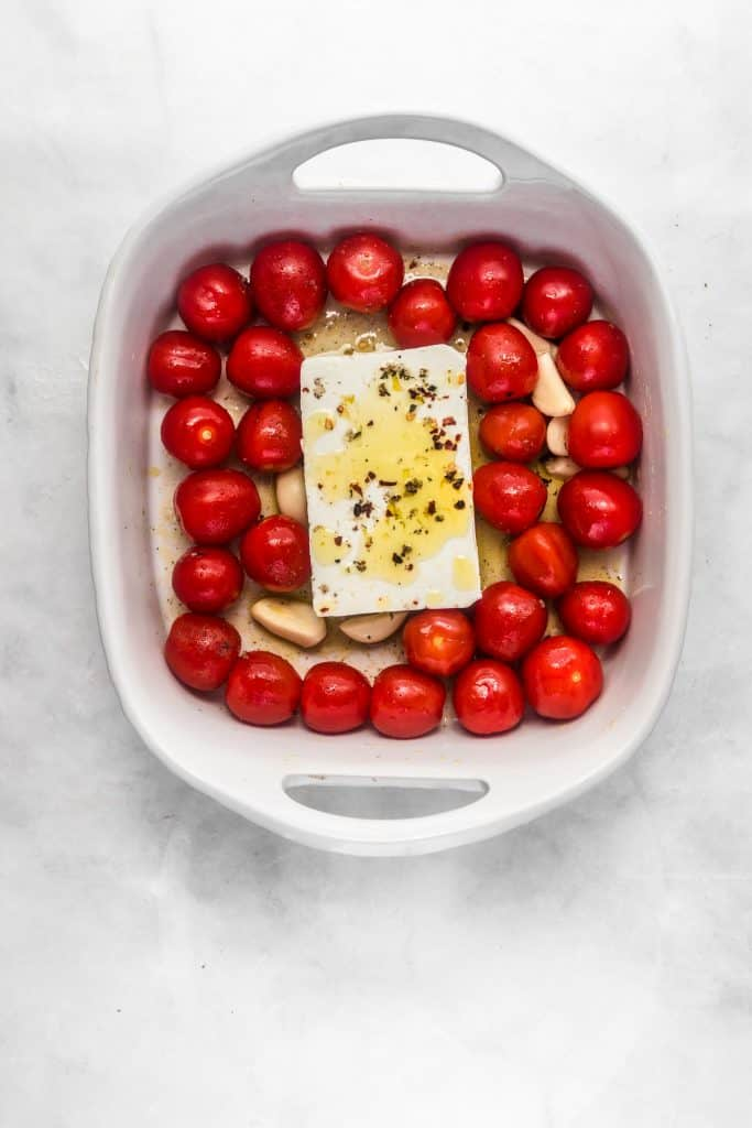 Block of feta on cherry tomatoes in a white serving dish